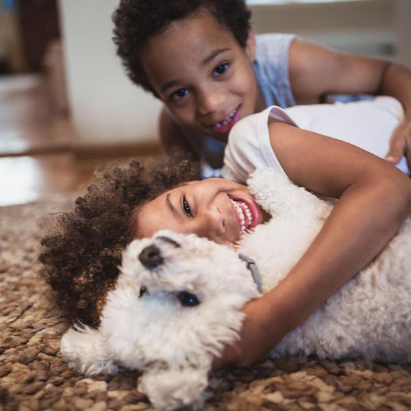 Cute mixed - race siblings having fun, playing at home with dog